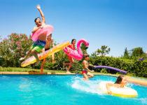 Amici felici che saltano in piscina durante un pool party