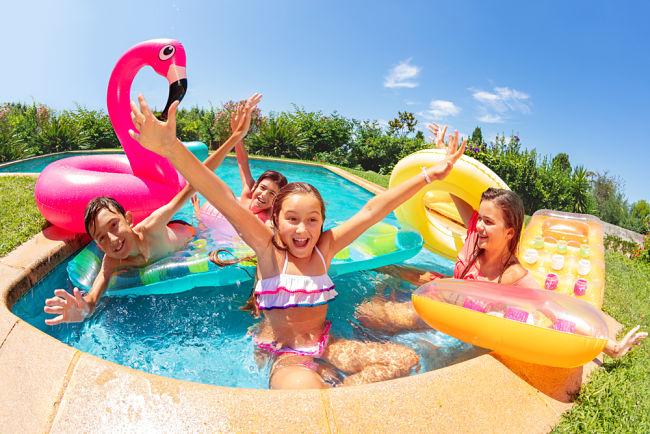 Bambini che si divertono insieme e che giocano in piscina durante una festa