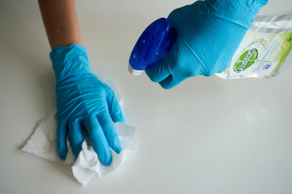 Mani che puliscono una superficie bianco-lucido