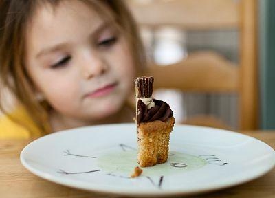 Bambina che guarda una fetta di torta ad un compleanno