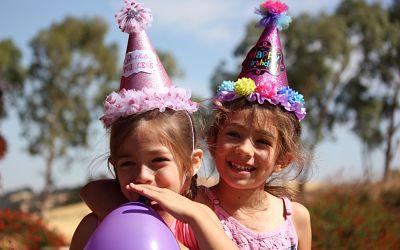 Bambine sorridenti con palloncino che si divertono ad una festa