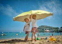 Bambini sotto l'ombrellone che giocano sulla spiaggia