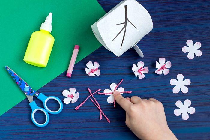 Mamma che sta creando fiori di Ibisco per decorare gli inviti a tema Oceania fai-da-te.