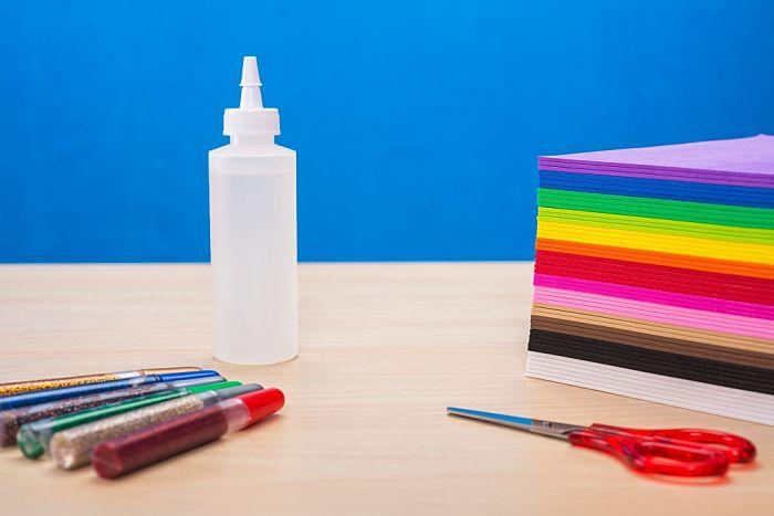 Materiale per inviti a tema Oceania fai-da-te: colla, cartoncini multicolore, glitter e forbici.