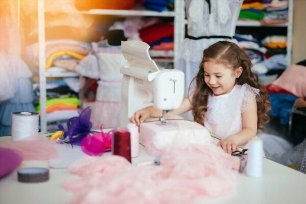 Bambina che si diverte durante un laboratorio di cucito