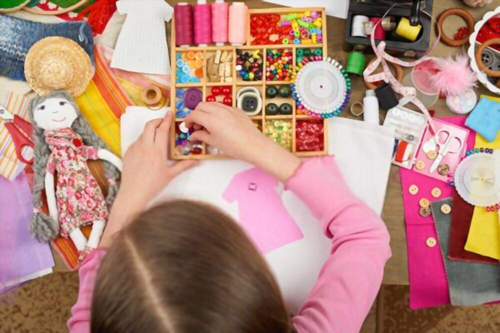 Bambina che sceglie come decorare il vestito appena realizzato per la sua bambola durante una festa dal sarto