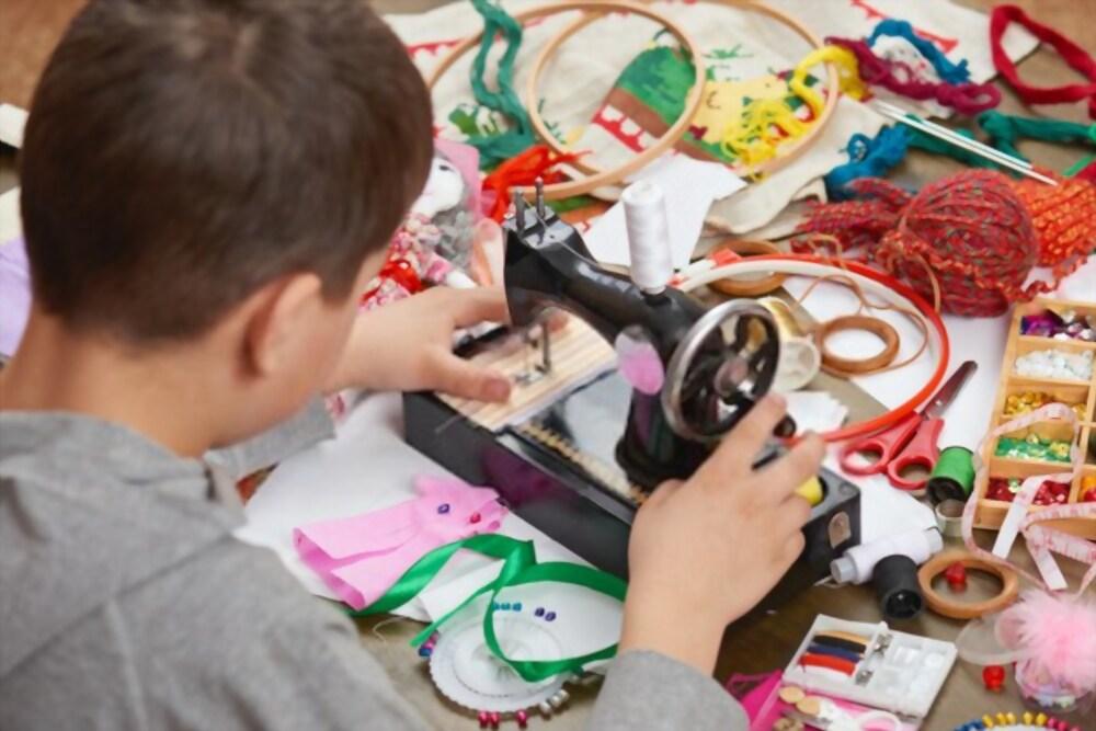 Bambino che usa una macchina da cucire durante una festa di compleanno dal sarto