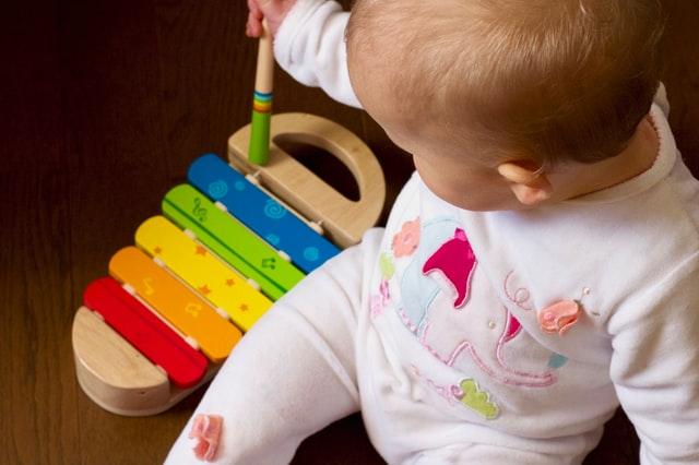 Bambino neonato che gioca con uno dei giochi musicali per bambini, lo xilofono
