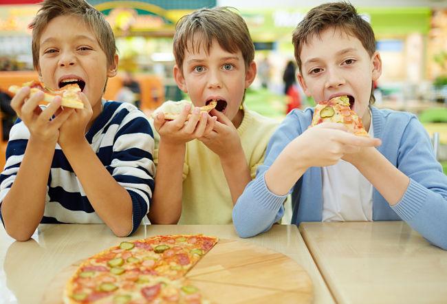 bambini grandi mangiano la pizza in pizzeria