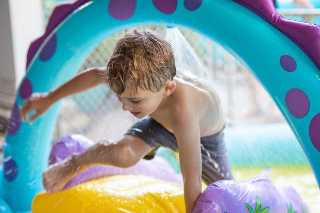 il bambino gioca sorridente al parco gioco gonfiabile