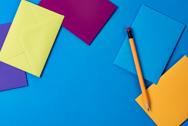 buste di carta colorate con matita su sfondo azzurro per uno dei giochi musicali per bambini