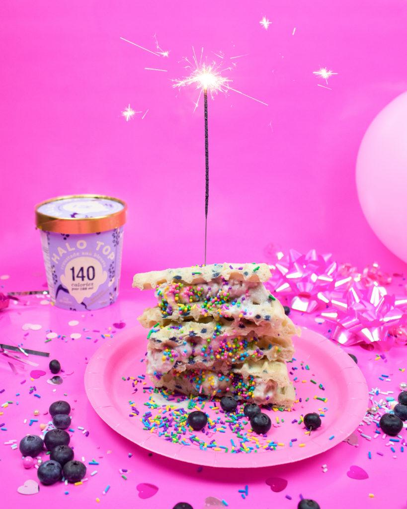 dolce su un piatto rosa decorato con more, glassa e zuccherini su uno sfondo rosa buffet per una festa di complanno per bambini.