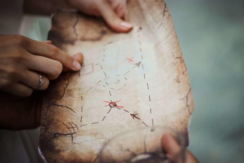 i bambini che espolorano la carta della caccia al tesoro durante una festa all'aperto