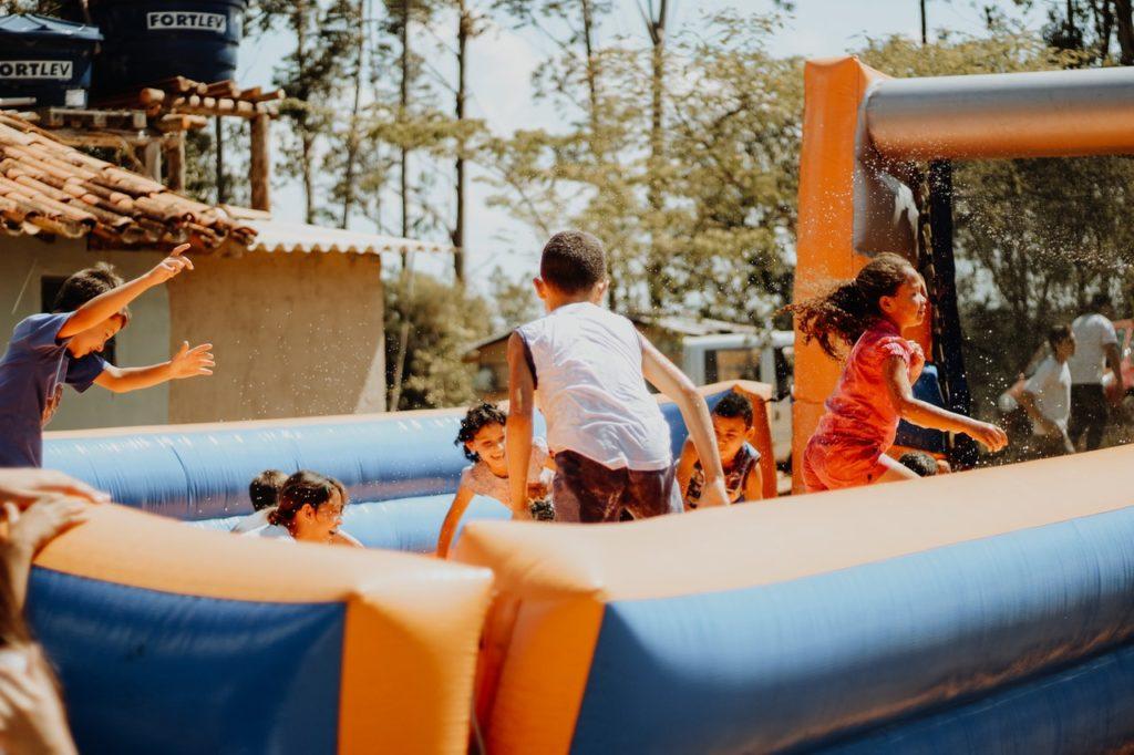 i bambini saltano felici al parco giochi gonfiabili