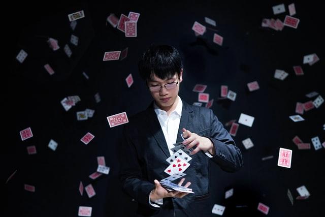 Mago con un mazzo di carte intento a fare uno dei suoi trucchi.