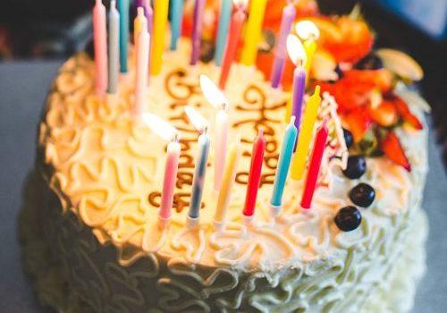 torta di compleanno con candeline accese e scritta happy birthday
