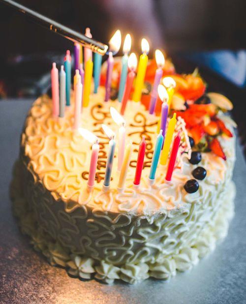 """Torta di compleanno con candeline accese e scritta """"happy birthday"""""""