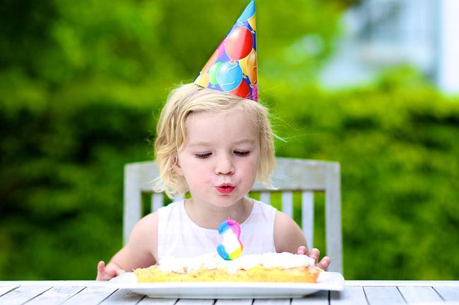 Bambina che festeggia il compleanno spegnendo le candeline