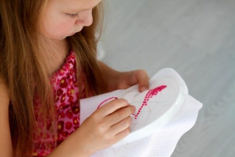 Bambina che ricama uno schema a punto croce durante un laboratorio sartoriale