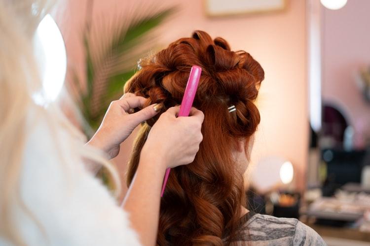 ragazza con capelli rossi che si fa fare i boccoli.
