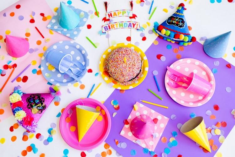 bicchieri e piatti di plastica, tovaglioli e berrettini per un compleanno.