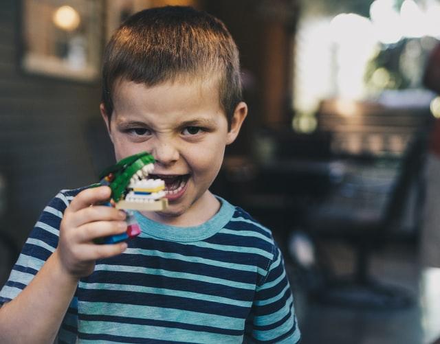 bambino che gioca con la testa di un dinosauro giocattolo, uno dei tanti regali di compleanno per bambini