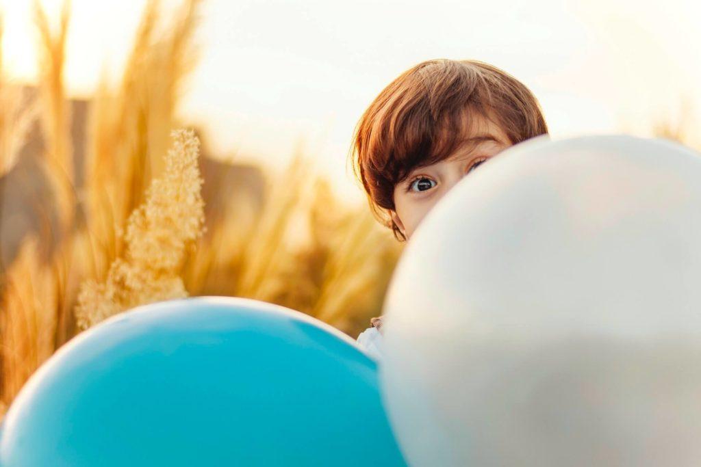 il bambino sorridente con i palloncini durante una festa al parco giochi gonfiabile