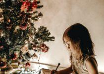 bambina scrive la letterina a babbo natale durante la festa a tema natale