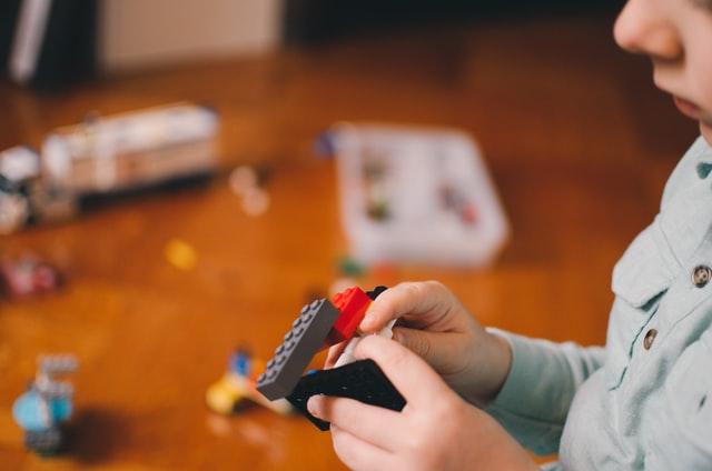 bambino che gioca con dei lego, perfetti regali di compleanno per bambini