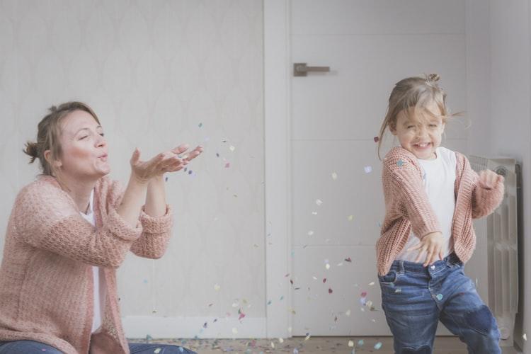 mamma e figlia vestite nello stesso modo con un giacchettino rosa che giocano con i coriandoli.