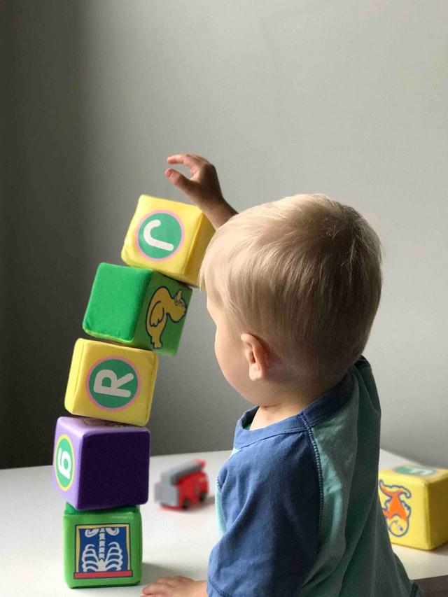 bimbo che gioca con dei cubi giocattolo, perfetti regali di compleanno per bambini