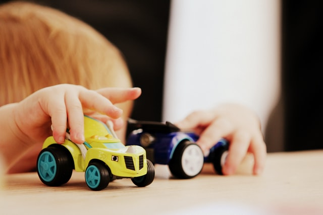 bimbo che gioca con due macchinine, perfetti regali di compleanno per bambini