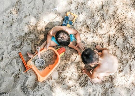 Bambini che giocano con la sabbia al mare