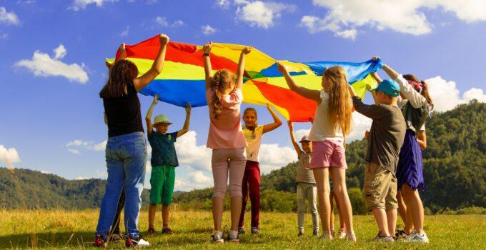 Giochi per bambini: gruppo di bambini che gioca all'aperto con telo